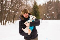 Älsklings- ägare, hund och folkbegrepp - barn som ler den caucasian mannen som rymmer den Jack Russell terriern utomhus- i vinter royaltyfria bilder