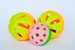 Älsklings- färgrik plast- leksakboll och klocka på vit bakgrund Fotografering för Bildbyråer
