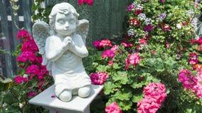 Älskvärd ängel med färgrika blommor i trädgården Royaltyfri Foto