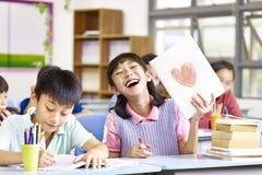 Älskvärd asiatisk skolflicka som visar hennes teckning royaltyfri foto