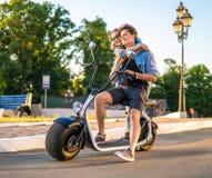 Älskvärd barnpardatummärkning med den elektriska cykeln royaltyfria bilder