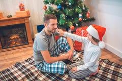 Älskvärd bild av flickan som trycker på näsan av hennes fader med fingret Hon ser honom och ler Ung man i pajamablickar royaltyfria foton