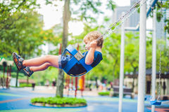 Älskvärd blond pys på en gunga i parkera Förtjusande pojke som har gyckel på lekplatsen arkivbilder