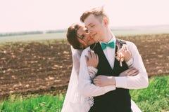 Älskvärd brudgum och brud på fältet Royaltyfria Bilder