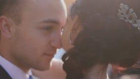 Älskvärd brudgum som rymmer och kysser försiktigt hans nya fru efter ceremoni Kameran lyfter långsamt från midja till framsidor lager videofilmer