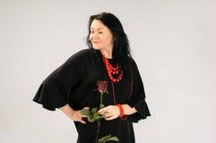 Älskvärd brunett i en svart klänning Kjolfladdrandena I hennes hand rymmer en kvinna en röd ros, henne har etniska röda pärlor arkivfoton