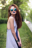 Älskvärd brunettflicka med blåa kanter i rund solglasögon Royaltyfri Bild