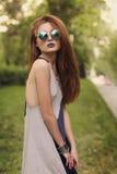 Älskvärd brunettflicka med blåa kanter i rund solglasögon Royaltyfri Foto