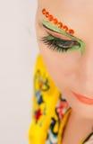 Älskvärd brunettkvinnastående med idérikt smink Arkivfoton