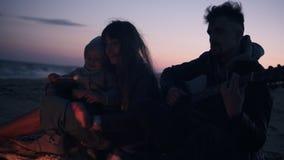 Älskvärd caucasian familj av tre som sitter bredvid brasan - fader som spelar gitarren, ung lång haired kvinnamatning lager videofilmer