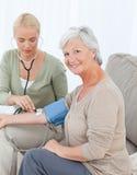 Älskvärd doktor som tar blodtryck Fotografering för Bildbyråer