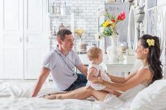 Älskvärd familj som tillsammans sitter på sängen Arkivbild