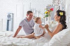 Älskvärd familj som tillsammans sitter på sängen Arkivbilder