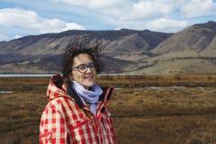 Älskvärd flicka av det europeiska utseendet i de sceniska bergen på Lake Baikal på våren på fältet under en stark vind och henne Fotografering för Bildbyråer