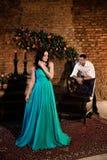 Älskvärd flicka i en lång klänning som står full längd royaltyfri fotografi