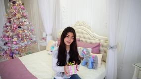 Älskvärd flicka i lynne för nytt år med gåvan i hand som ler på kameran och in sitter på säng i bakgrund av julgranen stock video