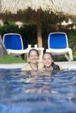 Älskvärd flicka och moder som spelar i simbassäng Royaltyfri Foto