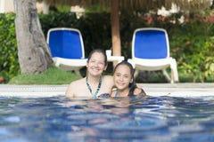 Älskvärd flicka och moder som spelar i simbassäng Arkivfoto