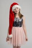Älskvärd flicka som ha på sig den röda Santa hatten royaltyfria bilder