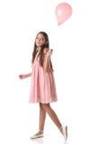 Älskvärd flicka som rymmer en rosa ballong Fotografering för Bildbyråer