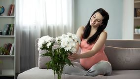 Älskvärd gravid dam som dekorerar huset med trevliga blommor, estetisk njutning arkivfoton