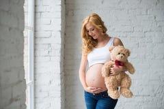Älskvärd gravid flicka med en nallebjörn Royaltyfri Foto