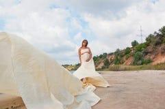 Älskvärd gravid flicka mot en bakgrund av vatten och himmel i en torkduk royaltyfri bild