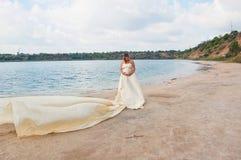 Älskvärd gravid flicka mot en bakgrund av vatten och himmel i en torkduk royaltyfria foton