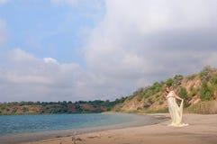 Älskvärd gravid flicka mot en bakgrund av vatten och himmel i en torkduk royaltyfria bilder