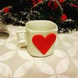 älskvärd kaffekopp under julgranen arkivbild