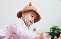Älskvärd kines behandla som ett barn flickan med en hattlekblomma royaltyfria bilder