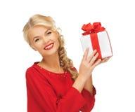 älskvärd kvinna i röd klänning med gåva Arkivbilder