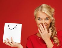 Älskvärd kvinna i röd klänning med shoppingpåsen Arkivfoton