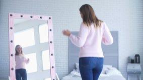 Älskvärd kvinna som beundrar hennes reflexion i spegel lager videofilmer