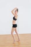 Älskvärd kvinna som hoppar over med repet i sportkorridor Fotografering för Bildbyråer