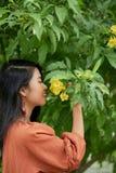 Älskvärd kvinna som luktar blomman arkivfoto