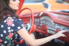 Älskvärd kvinna som poserar och och runt om en tappningbil fotografering för bildbyråer