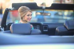 Älskvärd kvinna som poserar och och runt om en tappningbil Arkivfoto