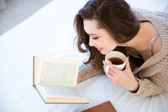 Älskvärd kvinnaläsebok och drickakaffe royaltyfria bilder