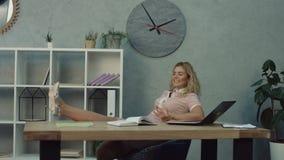 Älskvärd kvinnlig assistent som kopplar av i framstickandekontor stock video