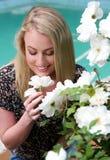 Älskvärd le blond dam och blommor Royaltyfria Bilder