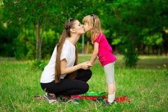 Älskvärd liten dotterkyssmoder Utomhus- stående av den lyckliga familjen Lycklig glädje för dag för moder` s royaltyfri fotografi