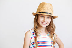 Älskvärd liten flicka med sugrörhatten på vit bakgrund Arkivbilder