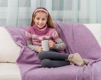 Älskvärd liten flicka på en soffa med den varma filten arkivfoto