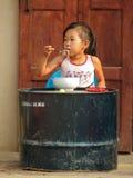 Älskvärd liten flicka som äter i gatan Arkivbild