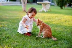 Älskvärd liten flicka som spelar med en katt på trädgård för grönt gräs Royaltyfria Bilder