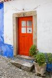Älskvärd ljus röd dörr med det fyrkantiga fönstret, stängda vitgardiner, med en farstubro av stora fyrkantiga stenar och en stenv Arkivbild
