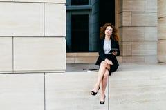 Älskvärd lockig kvinna med den säkra blicken och att sitta bara som visar hennes spensliga långa ben, iklätt svart omslag med kjo royaltyfria bilder
