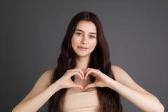 Älskvärd lycklig kvinnlig med brunetthår som visar förälskelsetecken med hennes köp händer i hjärtaform arkivfoto