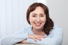 Älskvärd medelålders brunettkvinna med ett stråla leende som hemma som sitter på en soffa ser kameran royaltyfri foto